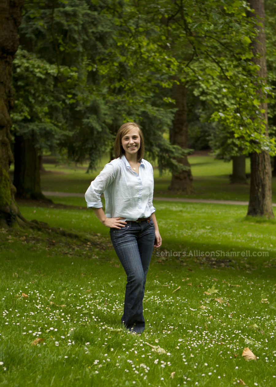 A high school senior in Portland, Oregon stands amongst trees and grass.