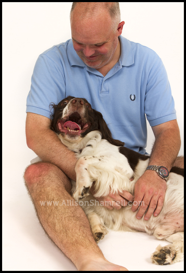 A man holds his English springer spaniel in the studio on white.