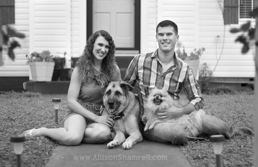 A family and their dogs sit in front of their house for a portrait.